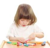Kleines Mädchen, das mit Lehm spielt. stockbild
