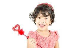 Kleines Mädchen, das mit Liebessymbol aufwirft Lizenzfreies Stockfoto