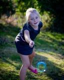 Kleines Mädchen, das mit Luftblasen spielt Lizenzfreie Stockfotografie