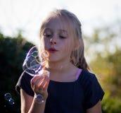 Kleines Mädchen, das mit Luftblasen spielt Stockbild