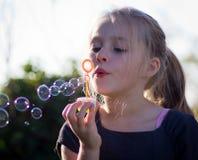 Kleines Mädchen, das mit Luftblasen spielt Stockfoto