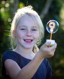 Kleines Mädchen, das mit Luftblasen spielt Stockfotos