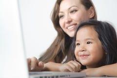 Kleines Mädchen, das mit Mutter lächelt Stockfotografie