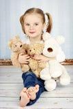 Kleines Mädchen, das mit Plüschspielwaren streichelt Stockbilder