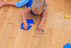 Kleines Mädchen, das mit Puzzlespiel, Früherziehung spielt Stockbild