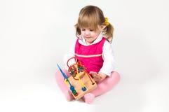 Kleines Mädchen, das mit Puzzlespielspielzeug spielt Lizenzfreie Stockfotos