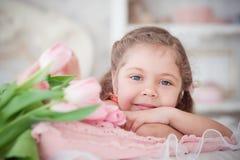 Kleines Mädchen, das mit rosa Tulpen liegt Lizenzfreies Stockfoto