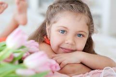 Kleines Mädchen, das mit rosa Tulpen liegt Stockfotografie