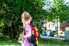 Kleines Mädchen, das mit Rucksack und Blumen geht stockfotografie
