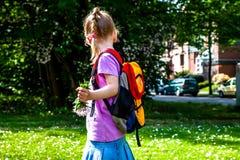 Kleines Mädchen, das mit Rucksack und Blumen geht lizenzfreie stockfotos
