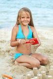 Kleines Mädchen, das mit Sand auf dem Strand spielt stockbild