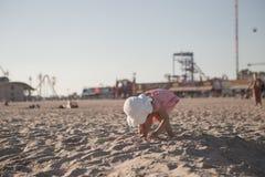 Kleines Mädchen, das mit Sand auf dem Strand spielt Lizenzfreie Stockfotos