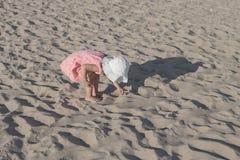 Kleines Mädchen, das mit Sand auf dem Strand spielt Stockbilder