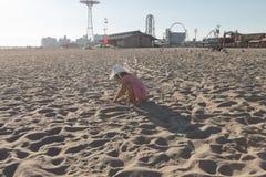 Kleines Mädchen, das mit Sand auf dem Strand spielt Lizenzfreies Stockbild