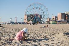 Kleines Mädchen, das mit Sand auf dem Strand spielt Stockfotografie