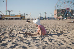 Kleines Mädchen, das mit Sand auf dem Strand spielt Lizenzfreies Stockfoto