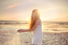 Kleines Mädchen, das mit Sand, Sonnenunterganghimmel auf adriatisches Seestrand in Albanien spielt Sand, der durch Finger gleitet lizenzfreie stockfotos