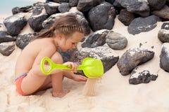 Kleines Mädchen, das mit Sand spielt Stockbilder