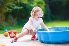 Kleines Mädchen, das mit Sand spielt Stockfoto