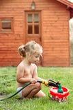 Kleines Mädchen, das mit Schlauch und Wasser spielt Stockbild