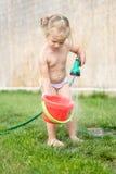 Kleines Mädchen, das mit Schlauch und Wasser spielt Stockfotografie