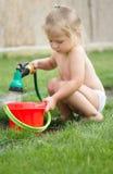 Kleines Mädchen, das mit Schlauch und Wasser spielt lizenzfreies stockbild