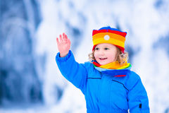 Kleines Mädchen, das mit Schnee im Winter spielt Stockbild