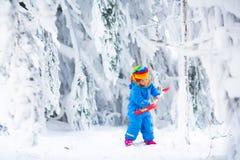Kleines Mädchen, das mit Schnee im Winter spielt Stockbilder