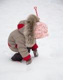 Kleines Mädchen, das mit Schnee spielt Stockbild