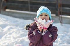 Kleines Mädchen, das mit Schnee spielt Lizenzfreie Stockbilder