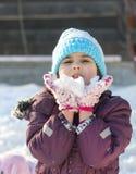 Kleines Mädchen, das mit Schnee spielt Stockbilder