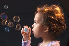 Kleines Mädchen, das mit Seifenluftblasen spielt Lizenzfreie Stockfotos