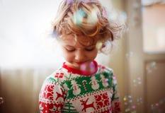 Kleines Mädchen, das mit Seifenluftblasen spielt Stockbild