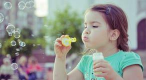 Kleines Mädchen, das mit Seifenluftblasen spielt Lizenzfreies Stockfoto