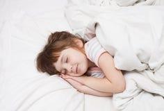 Kleines Mädchen, das mit seinen Händen unter seiner Backe schläft Stockbilder