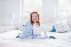 Kleines Mädchen, das mit Spielzeug spielt und ein Buch im Bett liest Stockfotos