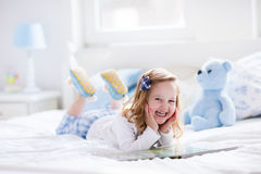 Kleines Mädchen, das mit Spielzeug spielt und ein Buch im Bett liest Lizenzfreies Stockbild