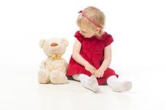 Kleines Mädchen, das mit Spielzeugbären spricht stockbilder