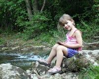 Kleines Mädchen, das mit Tablette aufwirft Stockfotos