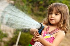 Kleines Mädchen, das mit Wasser spielt Stockbilder