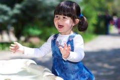 Kleines Mädchen, das mit Wasser spielt Lizenzfreie Stockfotografie