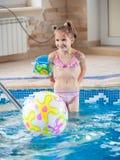 Kleines Mädchen, das mit Wasserball am Innenswimmingpool spielt Stockfotografie