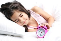 Kleines Mädchen, das mit Wecker schläft Stockfoto