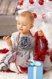 Kleines Mädchen, das mit Weihnachtsverzierungen spielt Lizenzfreie Stockfotos