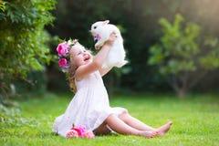 Kleines Mädchen, das mit wirklichem Kaninchen spielt Lizenzfreie Stockfotos