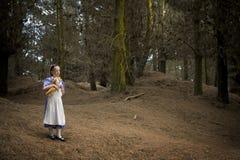 Kleines Mädchen, das mit Wunder im Wald geht Stockfoto