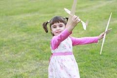 Kleines Mädchen, das mit zwei hölzernen Flugzeugen spielt Stockfotos