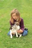 Kleines Mädchen, das mit zwei Welpen spielt Stockfotografie