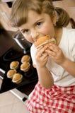 Kleines Mädchen, das Muffin isst lizenzfreie stockfotos
