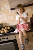 Kleines Mädchen, das Muffin isst stockfoto